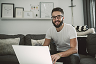 Young man sitting on couch, using laptop on coffee table - RAEF01742