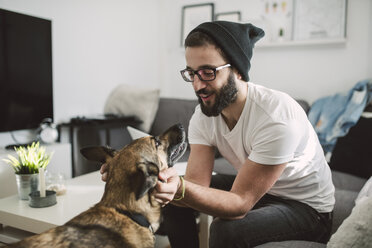 Young man at home tickling his dog - RAEF01745