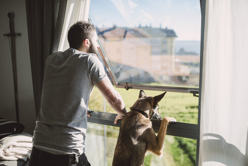 Young man standing at window with his dog, waiting - RAEF01748