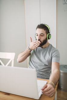 Young man wearing headphones, using laptop and blowing a kiss - RAEF01757