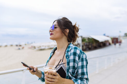 Young woman at the beach with cup of coffee and smart phone - GIOF02011