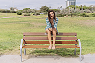 Young woman sitting on bench at the beach - GIOF02029