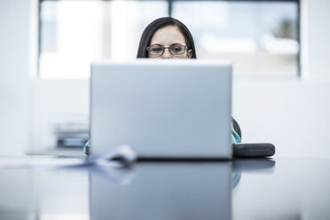 Woman with glasses using laptop in office - ZEF12975