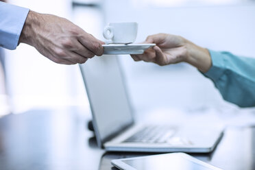 Person receiving a cup of coffee in a office - ZEF12978