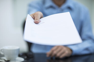 Person sitting at office desk holding a document - ZEF12984