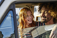 Smiling young woman looking at boyfriend in a car - FMKF03491