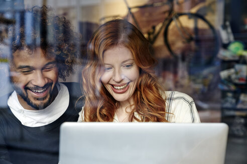 Happy young couple using laptop behind windowpane - FMKF03494