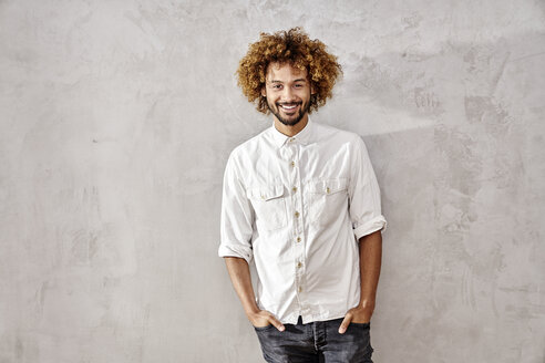 Portrait of smiling young man standing at grey wall - FMKF03503