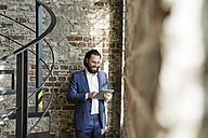 Smiling businessman using tablet at brick wall - FMKF03515