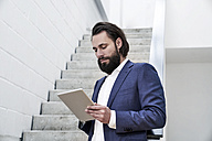 Businessman using tablet at stairs - FMKF03521