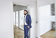 Portrait of confident businessman on empty office floor - FMKF03527