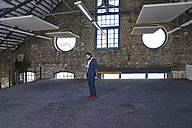 Businessman standing in a loft using cell phone - FMKF03536