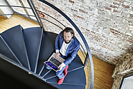Businessman using laptop on spiral staircase - FMKF03542