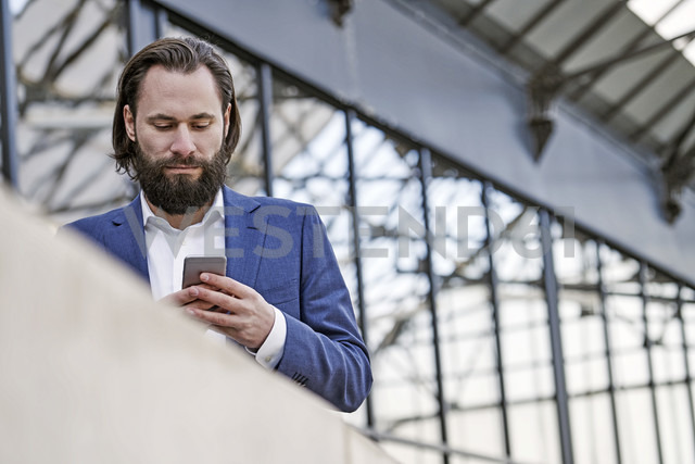 Businessman checking cell phone - FMKF03554