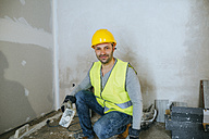 Portrait of construction worker holding a mallet - KIJF01257