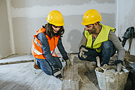 Male and female construction worker placing flooring - KIJF01260