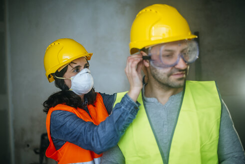 Woman helping man putting on safety glasses on a construction site - KIJF01263
