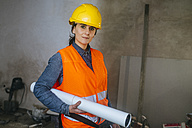 Woman wearing hard hat and reflective vest on construction site holding blueprint - KIJF01266