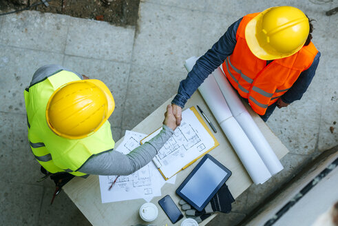 Woman and man in workwear shaking hands above construction plan - KIJF01272