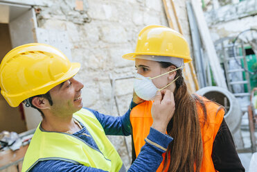 Man helping woman putting on dust mask on a construction site - KIJF01278