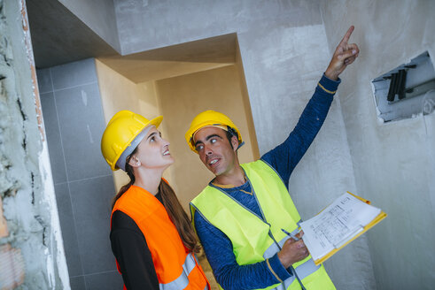 Construction worker showing electrical installation to woman - KIJF01281