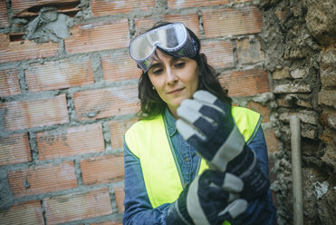 Woman on construction site putting on protective gloves - KIJF01290