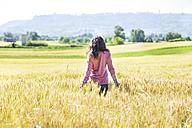 Back view of young woman standing in grain field - SIPF01424