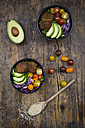 Lunch bowls of leaf salad, red cabbage, avocado, tomatoes and quinoa fritters - LVF05895