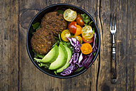 Lunch bowl of leaf salad, red cabbage, avocado, tomatoes and quinoa fritters - LVF05898