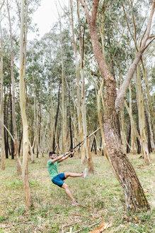 Man doing suspension traning outdoors - MGOF03002