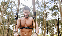Smiling barechested man doing suspension traning outdoors - MGOF03017