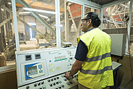 Worker in concrete factory pressing button on control panel - JASF01552
