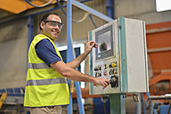 Worker in concrete factory pressing button on control panel - JASF01558