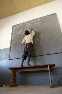 Madagascar, Fianarantsoa, Schoolboy writing on blackboard - FLKF00743