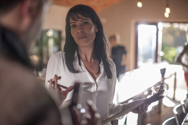 Woman holding clipboard in a restaurant - ZEF13006