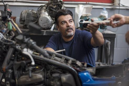 Two mechanics working on motorcycle in workshop - ZEF13018