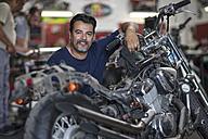 Portrait of smiling mechanic in motorcycle workshop - ZEF13027