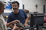 Two mechanics talking in workshop - ZEF13036