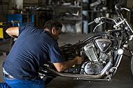Mechanic working on motorcycle in workshop - ZEF13042