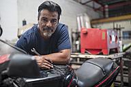 Portrait of confident mechanic in motorcycle workshop - ZEF13045