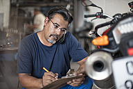 Mechanic with clipboard and phone in motorcycle workshop - ZEF13051