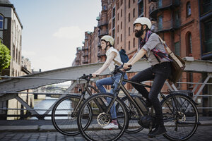 Germany, Hamburg, couple riding electric bicycles at Old Warehouse District - RORF00641