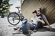 Germany, Hamburg, couple on bicycle trip having a rest looking at cell phone - RORF00644