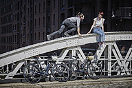Germany, Hamburg, couple with electric bicycles having fun on a bridge - RORF00647