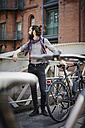 Germany, Hamburg, hipster with electric bicycle standing on a bridge at Old Warehouse District - RORF00650