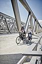Germany, Hamburg, couple riding electric bicycles on a bridge - RORF00662