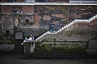 Germany, Hamburg, couple with electric bicycle relaxing at Old Warehouse District - RORF00668