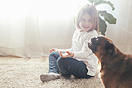 Happy little girl with her dog at home - RTBF00701