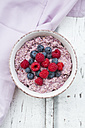 Bowl of overnight oats with blueberries and raspberries on wood - LVF05905