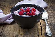 Bowl of overnight oats with blueberries and raspberries on wood - LVF05908